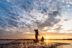 Силуэт рыболовов бросая сетчатую рыбную ловлю во времени захода солнца на w Стоковое Фото