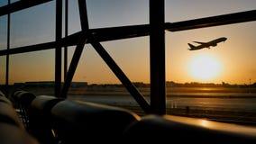 Силуэт самолета принимая на заход солнца на авиапорте Пекина на заднем плане окна стоковые изображения rf