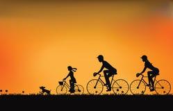 Силуэт семьи управляя велосипедом с красивым небом на заходе солнца иллюстрация штока