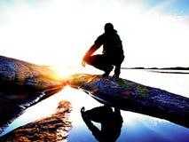 Силуэт сидя человека на каменистой береговой линии Hiker видя над заливом к выравнивать солнце стоковые изображения rf