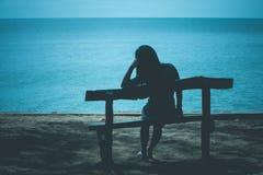 Силуэт сиротливой женщины сидя на деревянной скамье на пляже и смотря к голубому морю стоковая фотография rf