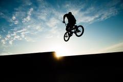 Силуэт скакать весьма человек велосипедиста на заходе солнца лета с космосом экземпляра Стоковое Изображение RF