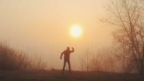 Силуэт смешных сумасшедших танцев человека против восхода солнца или захода солнца Успешные радостные и жизнерадостные танцы чело видеоматериал