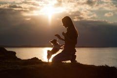 Силуэт собаки чихуахуа тренировки молодой женщины небольшой на красивой предпосылке захода солнца моря стоковая фотография rf