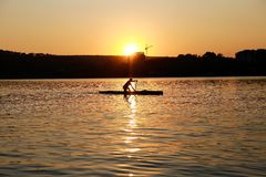 Силуэт сплавляясь на каяке человека на заходе солнца бесплатная иллюстрация