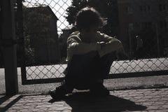 Силуэт спортивной площадки грустного предназначенного для подростков мальчика на открытом воздухе Чувствовать подавленный стоковые фотографии rf