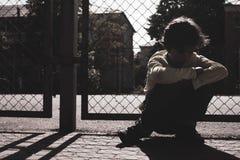 Силуэт спортивной площадки грустного предназначенного для подростков мальчика на открытом воздухе Чувствовать подавленный стоковое изображение rf