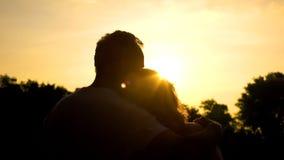 Силуэт старых обнимая пар, наблюдая захода солнца совместно, безопасная старость стоковая фотография rf