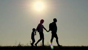 Силуэт счастливой семьи туристов идет с рюкзаками, держа руки во время захода солнца сток-видео