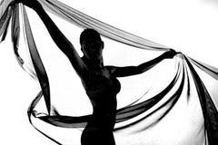 Силуэт танцев женщины с прозрачной тканью в черноте и