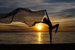 Силуэт тонкой сексуальной девушки представляя с шарфом на пляже Стоковое Изображение RF