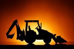 Силуэт трактора Backhoe, оранжевая предпосылка стоковое изображение
