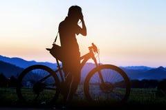 Силуэт фотографа в действии принимает фото с велосипедом на mou стоковое изображение
