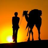 Силуэт человека и верблюда на заходе солнца Стоковое Изображение