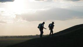 Силуэт человека 2 на верхней части горы с рюкзаками и другой шестерни выражая энергию и счастье 2 сток-видео