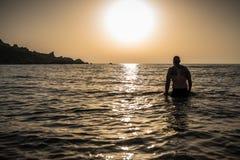 Силуэт человека на море на заходе солнца во время лета никто вокруг расслабленного и самостоятельно стоковые изображения