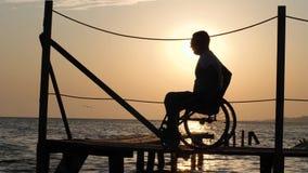 Силуэт человека с болея ногами на кресло-коляске на пристани наслаждаясь заходом солнца моря на перемещении лета сток-видео