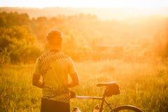 Силуэт человека с велосипедом Человек который наблюдает для захода солнца Стоковая Фотография