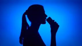 Силуэт чонсервной банкы женщины открытой безалкогольного напитка на красной предпосылке Женская сторона ` s в соде питья профиля акции видеоматериалы
