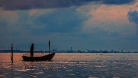 Силуэт obat рыбной ловли с установкой солнца в предпосылке с пасмурным красочным небом и солнечный луч starlight на воде отделыва Стоковое Изображение
