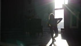 Силуэт ` s девушки танцует дома видеоматериал