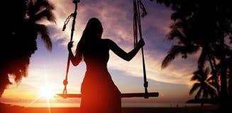 Силуэт ` s женщины сидя на качании и смотря заход солнца Стоковое Изображение