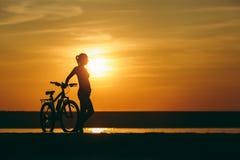 Силуэт sporty девушки в костюме стоя около велосипеда в воде на заходе солнца на теплый летний день релаксация pilates пригодност Стоковые Фото