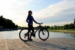 Силуэт sporty маленькой девочки стоя с велосипедом Стоковые Изображения