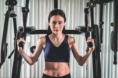 Сильная азиатская тренировка женщины на машине спортзала фитнеса Стоковые Фотографии RF