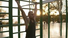 Сильная подходящая разминка человека вне на турниках outdoors Молодой человек тренируя подбрюшные мышцы поднимая ноги высокие к акции видеоматериалы