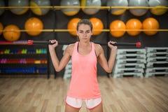 Сильная тренировка девушки с ручкой фитнеса Женщина в розовых sporty одеждах на запачканной предпосылке спортзала релаксация pila Стоковое Фото