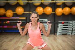 Сильная тренировка девушки с ручкой фитнеса Женщина в розовых sporty одеждах на запачканной предпосылке спортзала релаксация pila Стоковые Фото