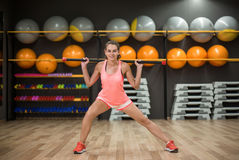 Сильная тренировка девушки с ручкой фитнеса Женщина в розовых sporty одеждах на запачканной предпосылке спортзала релаксация pila Стоковое фото RF