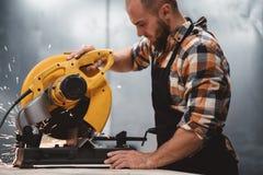 Сильный бородатый механик работая на электрическом угловом шлифовальном станке в фабрике механической обработки Работа в станции  стоковые фотографии rf