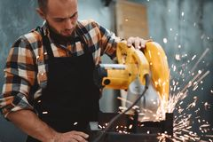 Сильный бородатый человек работая на электрическом угловом шлифовальном станке в фабрике механической обработки, искрах летает вр стоковые изображения