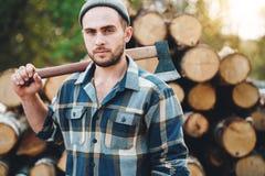 Сильный бородатый lumberman держит ось на его плече на складе журналов стоковая фотография rf