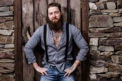 Сильный зверский человек с бородой и татуировки на его руках одетых в стильных представлениях случайных одежд на предпосылку  стоковое фото rf