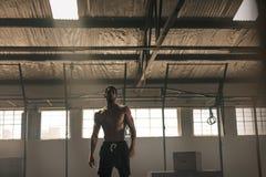 Сильный молодой человек с мышечным телом в спортзале стоковая фотография