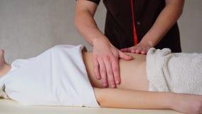 Сильный мужской masseur с нежными движениями руки замешивает живот женщины ` s клиента, которая лежит в комнате косметологии сток-видео