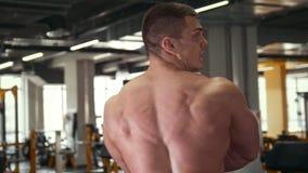 Сильный мышечный без рубашки человек перед зеркалом в спортзале сток-видео
