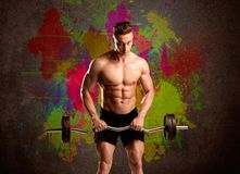 Сильный парень с красочными стеной и весом краски Стоковые Изображения