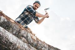 Сильный работник лесопогрузчика режет дерево в лесе стоковое изображение