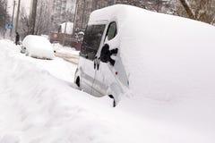 Сильный снегопад в городе и покрытом снег автомобиле стоковое изображение