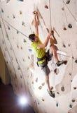 Сильный спортсмен взбираясь искусственная стена в bouldering спортзале внутри помещения стоковые изображения