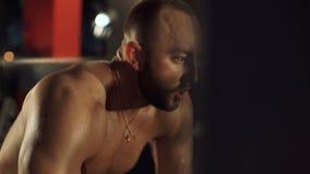 Сильный спортсмен отдыхает после разминки в спортзале 4K видеоматериал