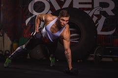 Сильный спортсмен парня, стойки в статическом баре на вытянутых руках и гантели тяжелого метала повышений Стоковое Изображение