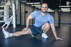 Сильный спортсмен подготавливая мышцы перед тренировкой Мышечный спортсмен делая работать в спортзале мужской протягивать Професс стоковая фотография rf