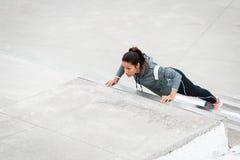 Сильный фитнес городская женщина делая уклон нажимает поднимает на го стоковое фото rf