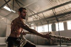 Сильный человек вытягивая тяжелую веревочку на спортзале Стоковые Фотографии RF