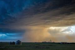Сильный шторм дует облака пыли над сельскохозяйственными угодьями с загораться заходящего солнца стоковые фотографии rf